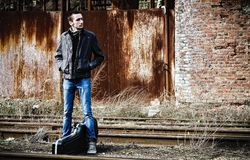 Young man with guitar case waiting for train among industrial ruins Stock Photo