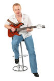 Young man with guitar on chair Stock Photos