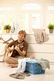 Young man with guitar and laundry Royalty Free Stock Images