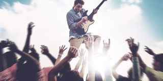 Young Man Guitar Performing Concert Ecstatic Crowds Concept.  royalty free stock image