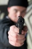 Young man with a gun. Young man pointing a gun straight at the camera. Focus is on the gun Royalty Free Stock Images