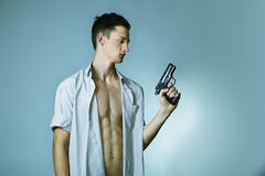 Young man with gun. Young man with shaped body posing in studio with handgun for like criminal portraits Royalty Free Stock Images