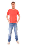 Young man guy red t-shirt jaens with hands in pockets isolated Royalty Free Stock Image