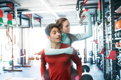 Young man in gym carrying woman on his shoulders. Royalty Free Stock Photography