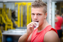 Young man in gym eating cereal bar Royalty Free Stock Image