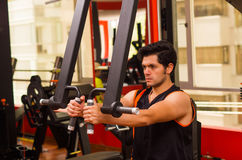 Young man in the gym and exercising Back on machine.  Stock Images