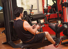 Young man in the gym and exercising Back on machine Royalty Free Stock Image