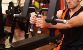 Young man in the gym and exercising Back on machine Stock Image
