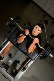 Young man in the gym exercising biceps with barbell Stock Photo