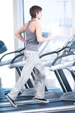 Young man at the gym exercising. Running Stock Photo