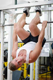 Young man in gym hanging upside-down to exercise abs Royalty Free Stock Photo