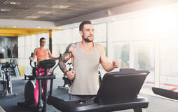 Young man in gym run on treadmill Royalty Free Stock Photos