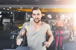 Young man in gym run on treadmill Stock Images