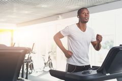 Young man in gym run on treadmill. Young happy handsome african-american man in fitness club. Cardio workout, running on treadmill. Healthy lifestyle, guy Royalty Free Stock Photos