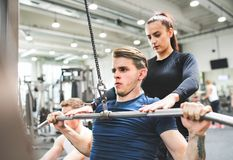 Young man in gym working out on pull-down machine, a personal trainer behind him. royalty free stock photo