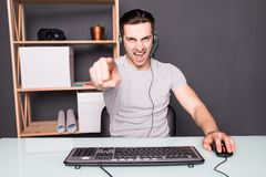 Young man or hacker in headset and eyeglasses with pc computer playing game and streaming playthrough or walkthrough video pointed. Technology, gaming, let`s Royalty Free Stock Image