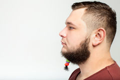 Young man with hair clips on beard. Young man portrait in profile with hair clips on long beard over gray background Stock Photo