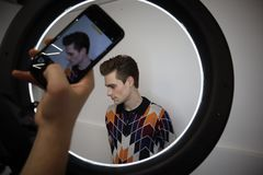 Young man after a haircut. Studio portrait being photographed after a haircut at the hairdresser Round LED Circle Lamp royalty free stock images