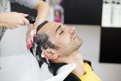 Young man at hairdresser Stock Image