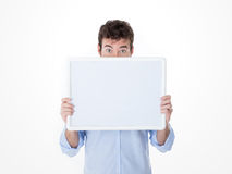 Young man with half face cover by an empty board. One guy hiding his head with a white banner royalty free stock image