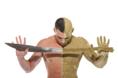 Young man half smeared with clay with sword\ Royalty Free Stock Photos