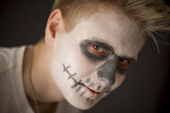 Young man in Halloween makeup. Young man in Halloween or skull makeup with dark red rimmed eye sockets as he prepares to celebrate the Day of the Dead or Royalty Free Stock Image