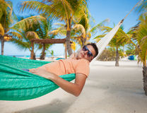 Young man in hammock on the exotic tropical resort. This image has attached release Royalty Free Stock Photos