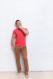 Young Man Hand On Chin Look Up To Copy Space Standing Over Wall Stock Photo