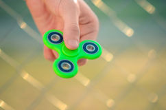 Young man hand holding antistress gadget fidget spinner. Teenager playing with green spinner outdoors on the rabitz grid bokeh. Shallow DOF Stock Photo