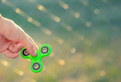Young man hand holding antistress modern gadget fidget spinner. Teenager playing with green spinner outdoors on the rabitz grid bokeh. Shallow DOF Stock Photography