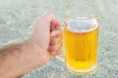 Young man hand holding a refreshing beer on the beach Stock Images