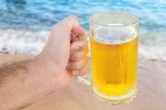 Young man hand holding a refreshing beer on the beach with wave Stock Images