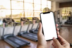 Young man Hand holding smartphone in gym to fitness phone fitne stock photo