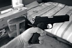 Young man hand holds a 9mm gun. In his bedroom Royalty Free Stock Photo