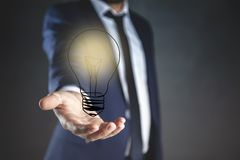 Young man hand light bulb in screen royalty free stock photography
