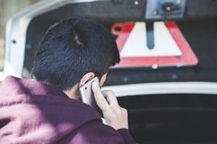 Man hand phone with broken car. Young man hand phone with broken car royalty free stock photo