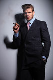 Young man with hand in pocket  is smoking a cigar Royalty Free Stock Photo