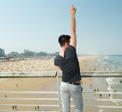 Young man with hand raised pointing up, beach in background Stock Images