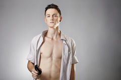 Young man with handgun. Young man with shaped body posing in studio with handgun for like criminal portraits Stock Photos