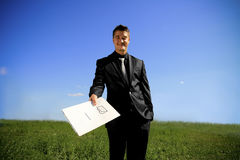 Young man handing a folder. Business man in the middle of the field handing a folder stock photos