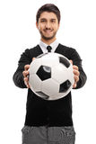 Young man handing a football towards the camera. Isolated on white background Stock Photo