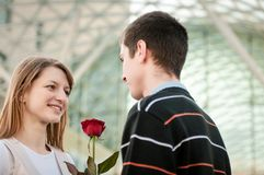 Young man handing over a flower to woman Royalty Free Stock Images