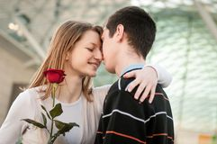 Young man handing over a flower to woman Royalty Free Stock Image