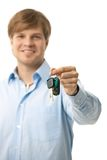 Young man handing over ignition keys. Selective focus on keys, isolated on white Royalty Free Stock Photography