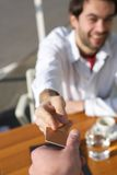 Young man handing a waiter payment card at restaurant Royalty Free Stock Images