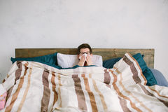 Young man with handkerchief. Sick guy on the bed has runny nose. man makes a cure for the common cold Stock Image