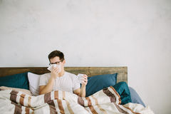 Young man with handkerchief. Sick guy on the bed has runny nose. man makes a cure for the common cold stock images