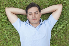 Young man with hands behind head lying on grass Stock Photos