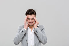 Young man with hands on temples suffering from headache Stock Photos