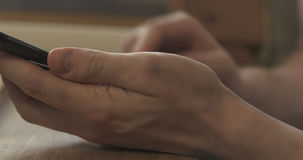 Young man hands using smartphone sitting at the table closeup Stock Photo